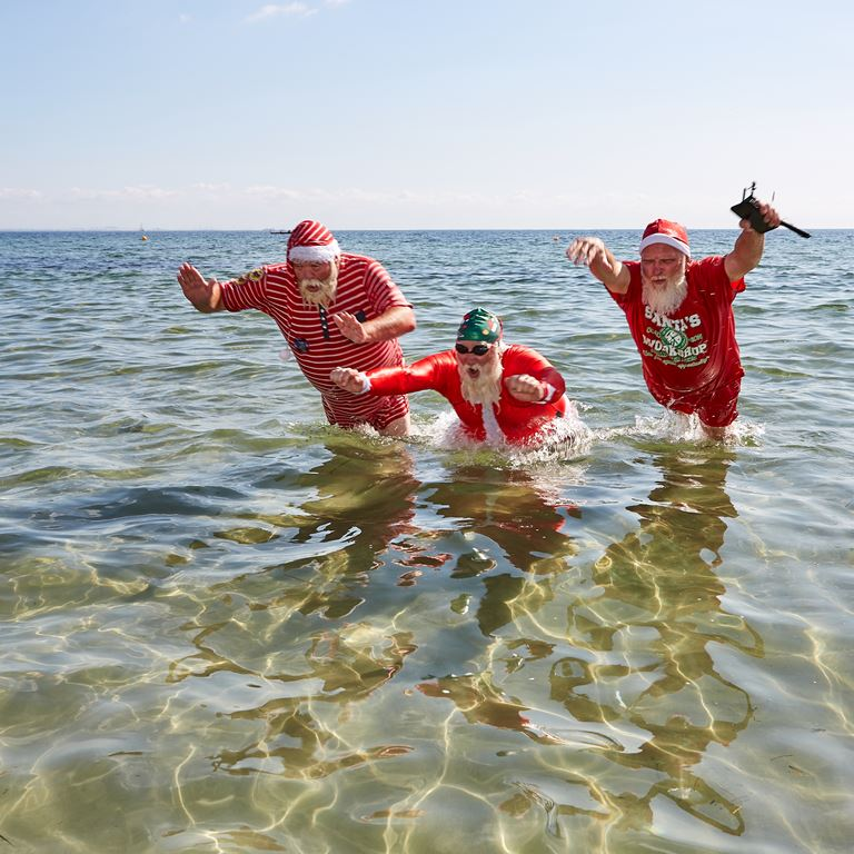 Santas from all around the world meet for their annual footbath at Bellevue Beach during World Santa Claus Congress 2019 at Bakken