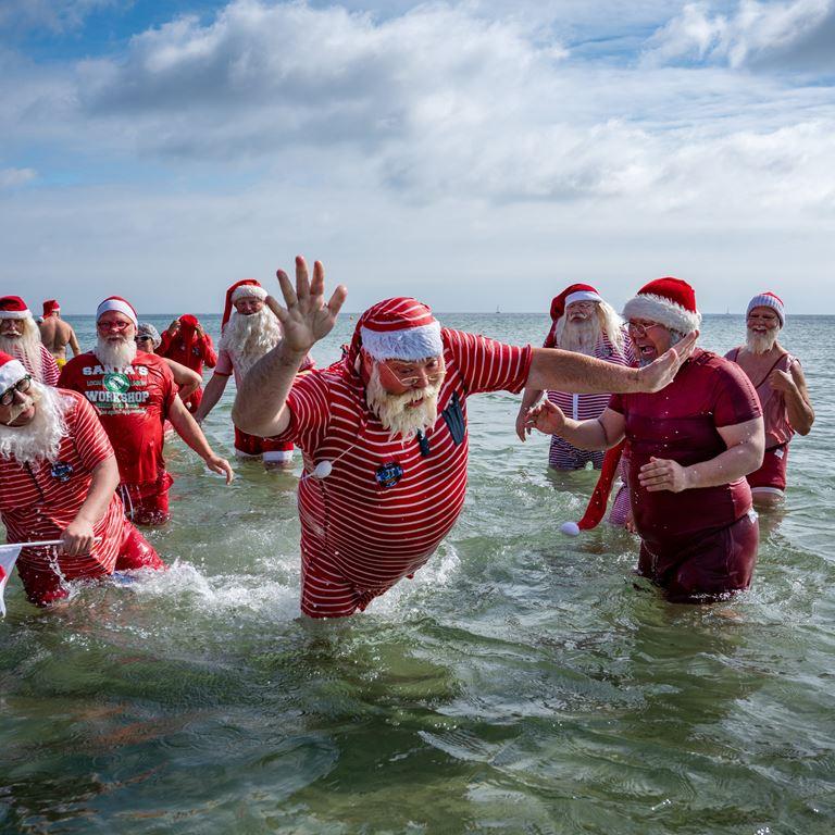 Julemænd fra hele verden mødes til et fodbad ved Bellevue Strand under Julemændenes Verdenskongres på Bakken.